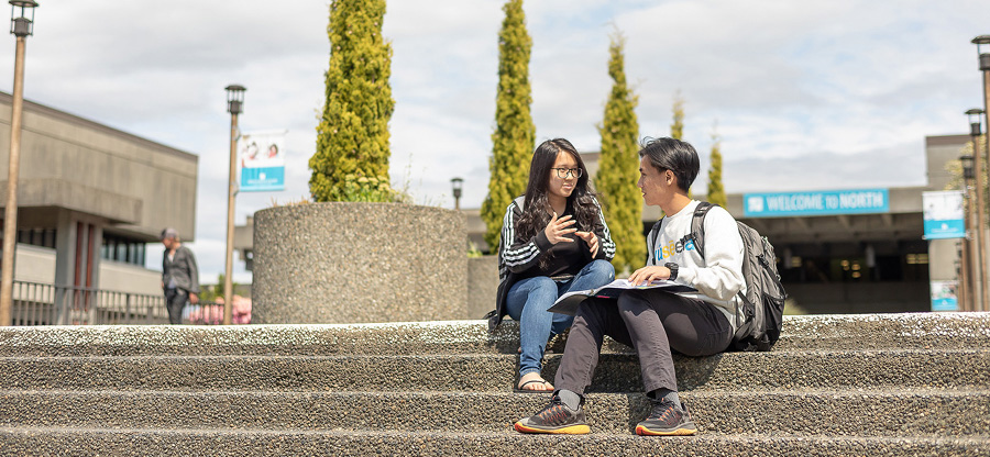North Seattle College students sitting on front steps