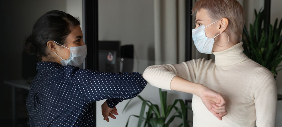 two women wearing face masks to help prevent COVID-19